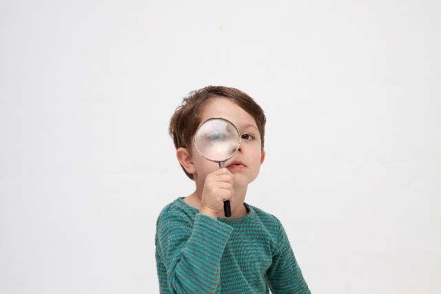 虫眼鏡で「プライムイングリッシュの口コミ評判」を探す少年