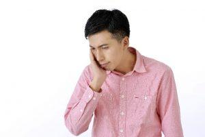 頭を抱える男性 英語圏にいても英語が話せるようにならないで悩む人も多い