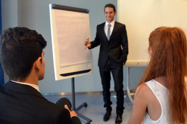 ミーティングで説明する男性 ビジネスの場では、論理的に英語で説明する力が求められる